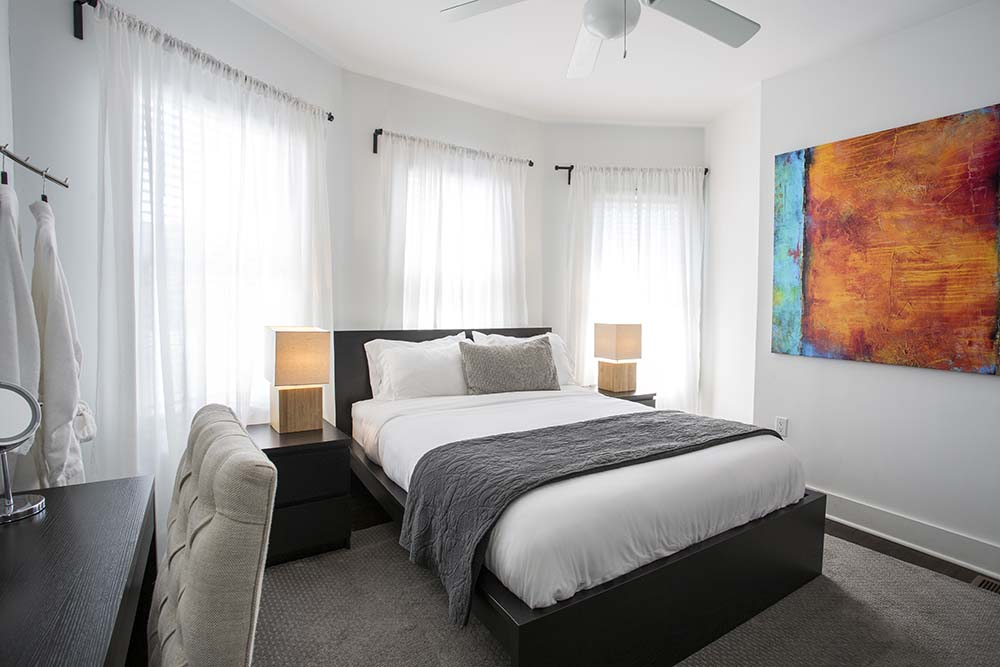Bedroom with bed and a abstract painting on the wall