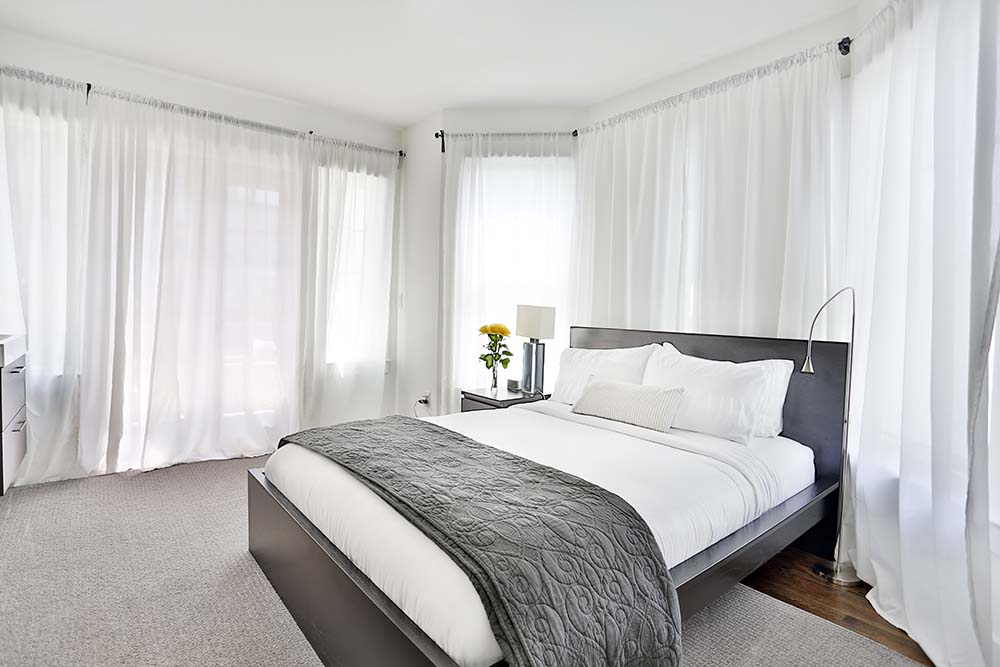 Queen bed in room with many windows