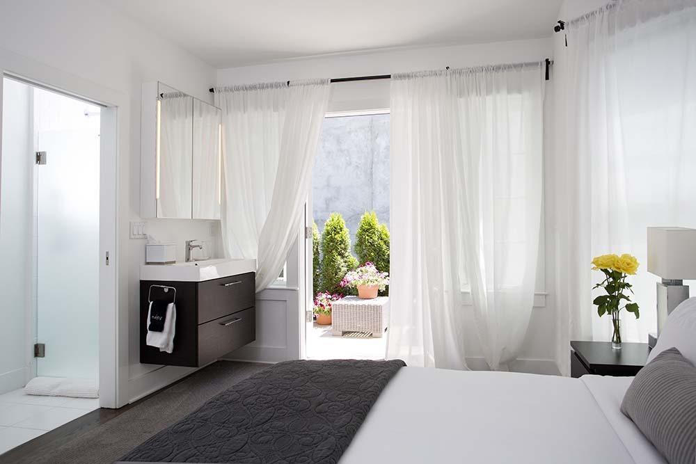 bedrooom with bed, vanity and a open door leading to patio