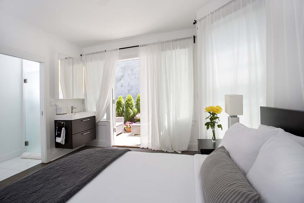 bedroom with large windows with white curtains, bed and vanity