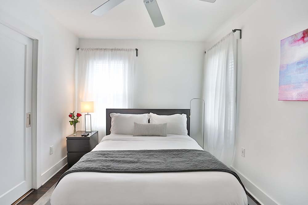 Bedroom with bed and 2 large windows