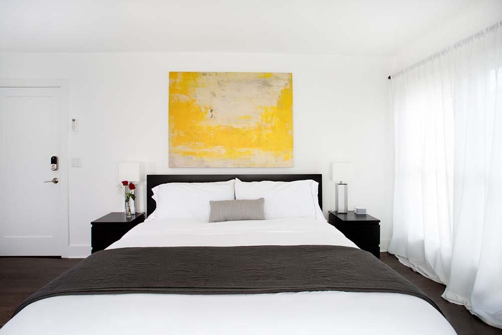 bed with white and black accessories and large yellow painting