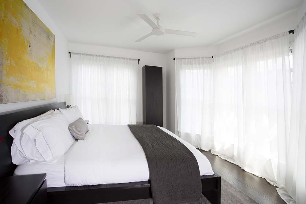 bedroom with large windows, white curtains and bed