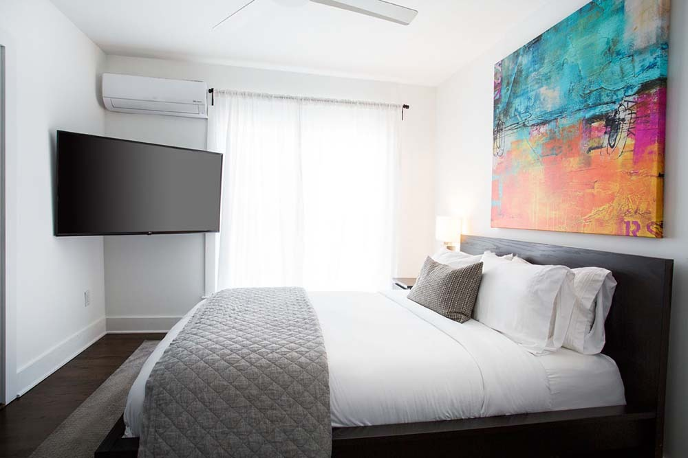 small room with bed, TV and large painting
