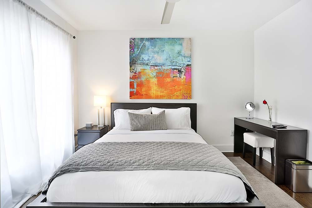 large painting on wall of bedroom with bed and desk